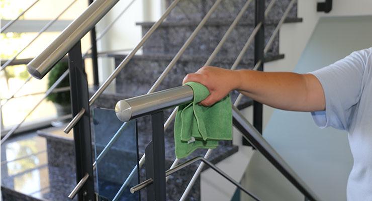 Treppenhausreinigung - Das Bild zeigt eine Frauenhand, die einen Treppen Handlauf reinigt.